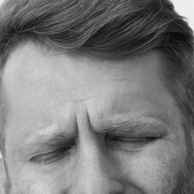 Close-up shot of redhead man with beard feeling pain in teeth, frowning and making suffering expression with closed eyes, touching cheek, having need to call dentist for curing decay or rotten tooth. Health and dental problems concept